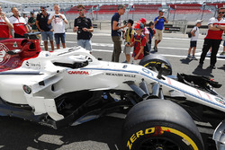 Fans take pictures of the Marcus Ericsson Sauber C37, under the supervision of Sauber team members