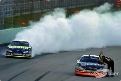 2004 NASCAR NEXTEL Cup champion Kurt Busch is brought the champion flag while race winner Greg Biffle celebrates