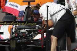 Crew members work on the car of Borja Garcia