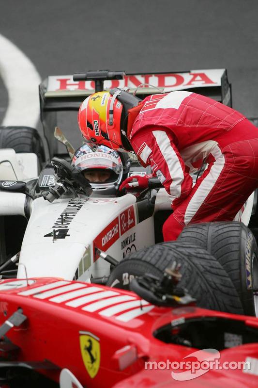 Michael Schumacher has a talk with Takuma Sato