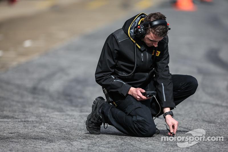 Pirelli tyre techncian takes a track temperature reading