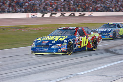 Greg Biffle and Jimmie Johnson drive through pit road after Biffle's spin