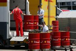 Ferrari team member unloads Shell fuel barrels
