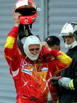 Michael Schumacher takes his helmet off