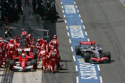 Kimi Raikkonen exits pitlane as Felipe Massa pits