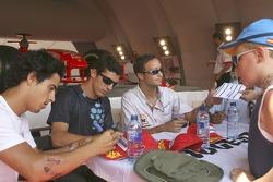 Andreas Zuber, Jose Maria Lopez and Lucas Di Grassi sign autographs in the Bridgestone tent