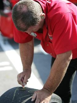 Gainsco/ Blackhawk Racing crew member marks tires