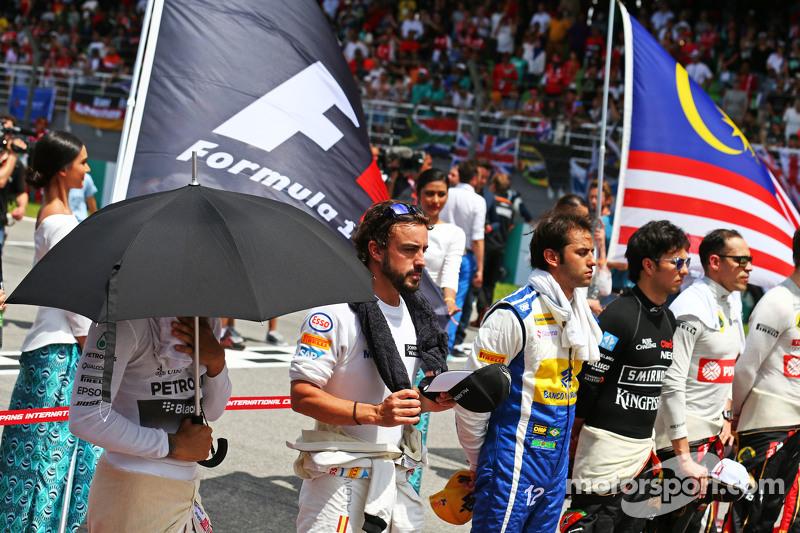 Lewis Hamilton, Mercedes AMG F1, und Fernando Alonso, McLaren, bei der Nationalhymne in der Startauf