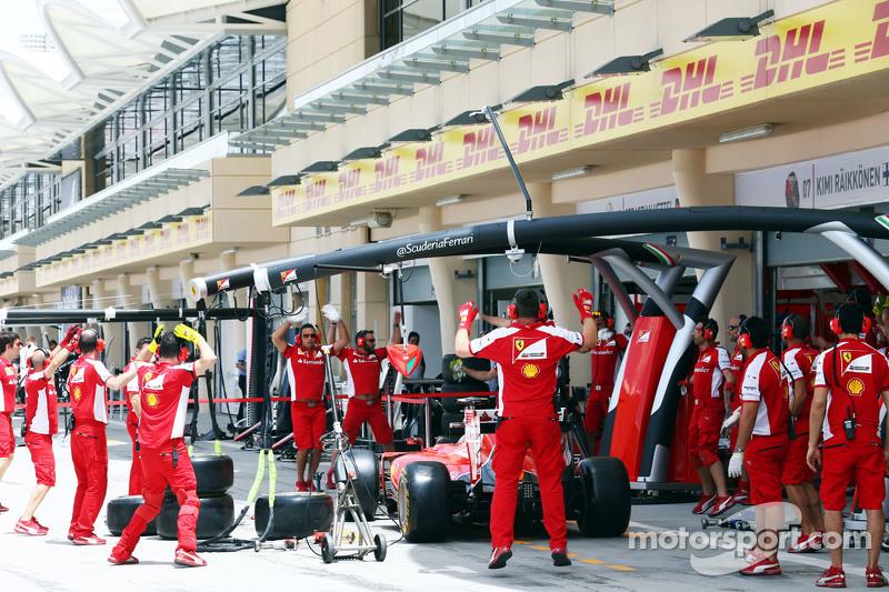 Ferrari mechanics perform some warm up exercises.