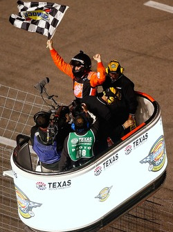Race winner Tony Stewart celebrates on the flag stand after climbing up the fence