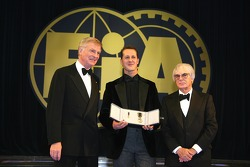 FIA President Max Mosley and FOM President Bernie Ecclestone present Michael Schumacher with the FIA Academy Gold Medal