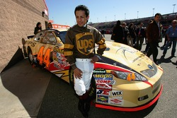Victor Espinoza, professional horse jockey, stands next to the #44 UPS Toyota