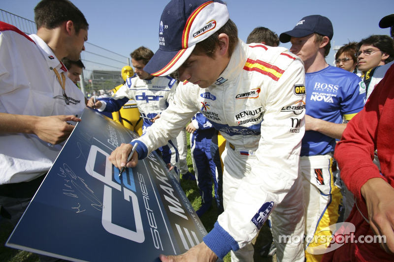 Vitaly Petrov signs the road safety board
