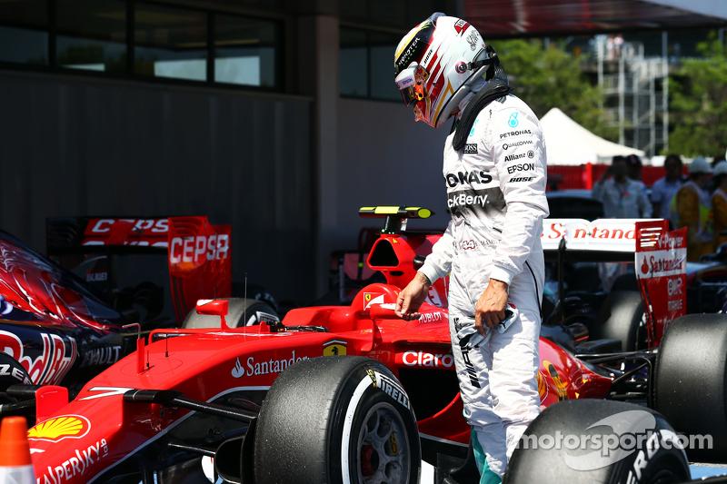 Lewis Hamilton, Mercedes AMG F1, sieht sich den Ferrari SF15-T von Kimi Räikkönen, Ferrari, im Parc Fermé an