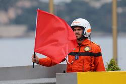 Sportwart schwenkt die rote Flagge zum Signal des Abbruchs der Session