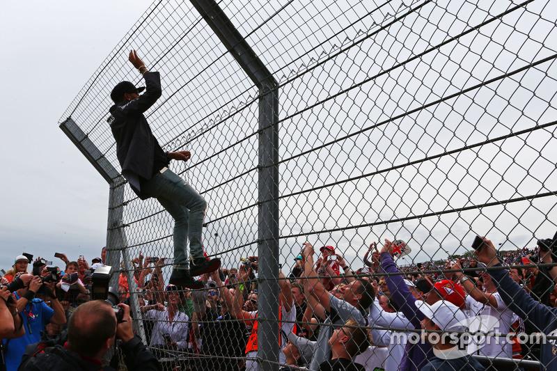Lewis Hamilton, Mercedes AMG F1, klettert am Zaun hoch, um die Fans zu grüßen