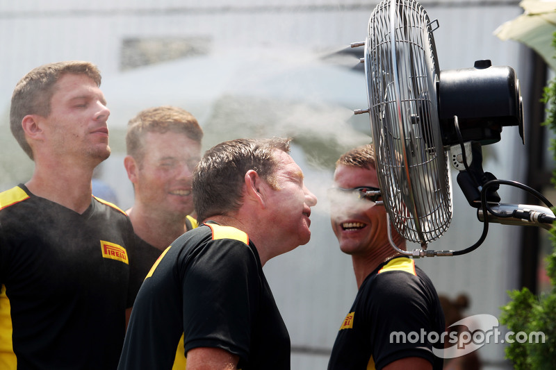 Pirelli tyre technicians cool themselves with misted fans in the paddock