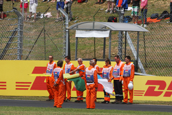 Marshals observe the pre-race tribute to Jules Bianchi