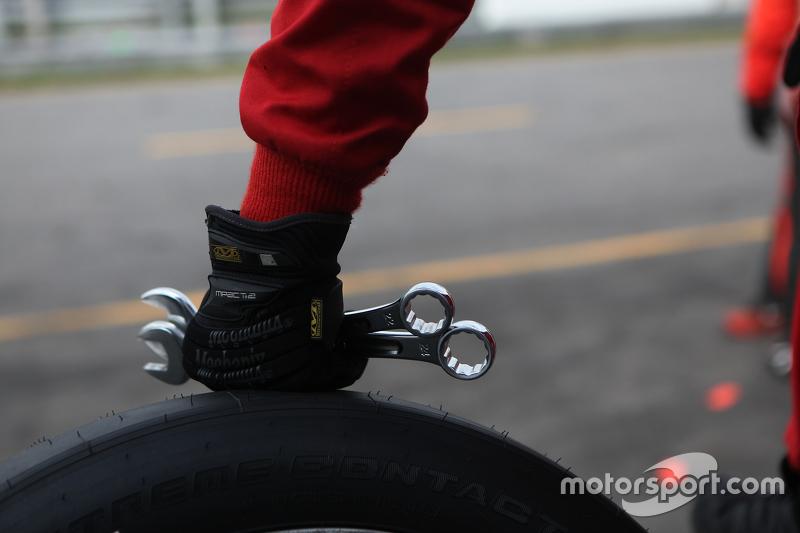 Kru mempersiapkan untuk bekerja pada mobil balap