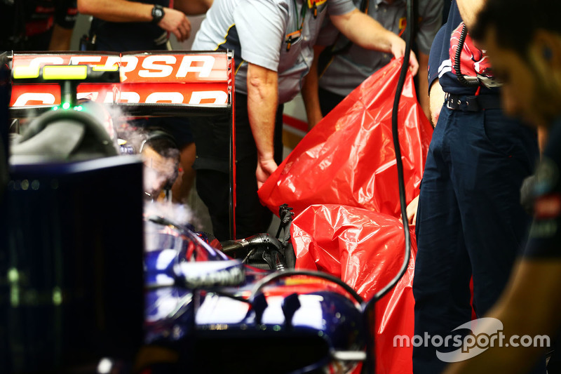 Pirelli engineers remove the damaged rear tyre of Carlos Sainz Jr., Scuderia Toro Rosso STR10 in the