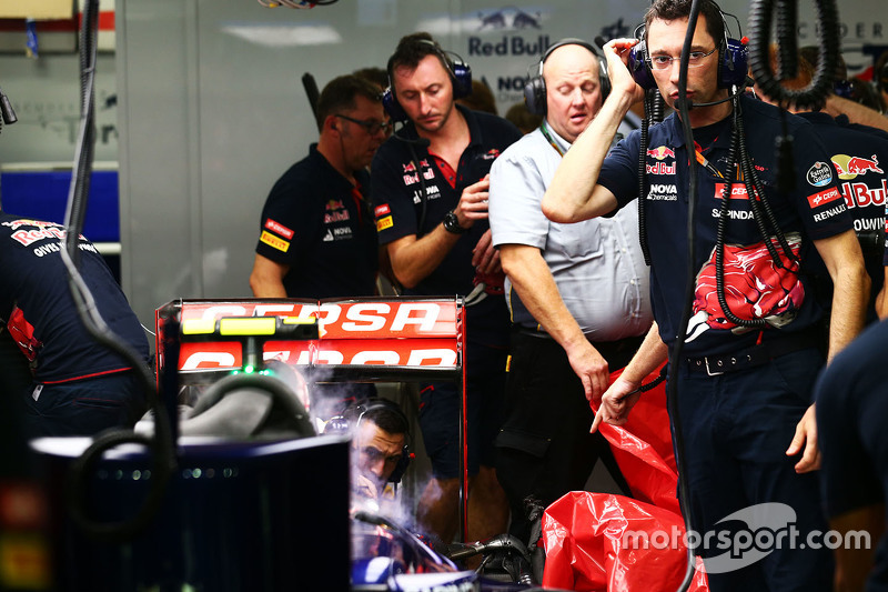 Pirelli інженери remove the damaged rear tyre Карлоса Сайнса мол., Scuderia Toro Rosso STR10 в другій практиці