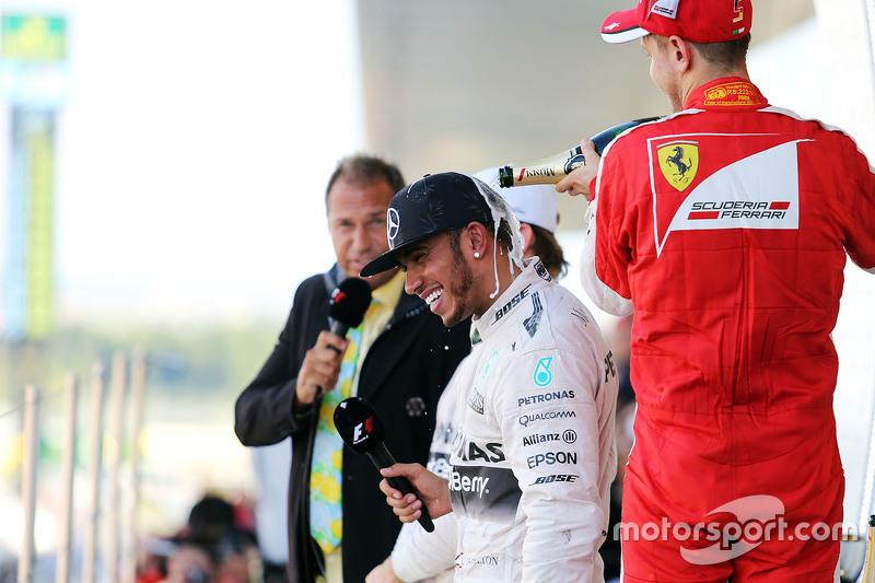 Race winner Lewis Hamilton, Mercedes AMG F1 celebrates on the podium with third placed Sebastian Vet