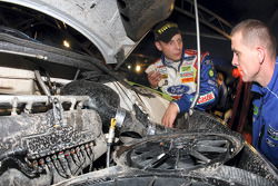 Mikko Hirvonen checks the engine bay on his Ford Focus RS WRC