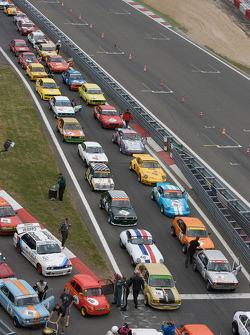 Vintage cars sit on pit road