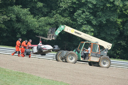 Corner workers work to remove Mark Olson's car from the race course
