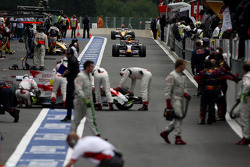 Mark Webber traverse une voie des stands peuplée