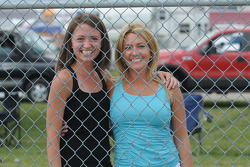 Two lovely ladies pose through the fence