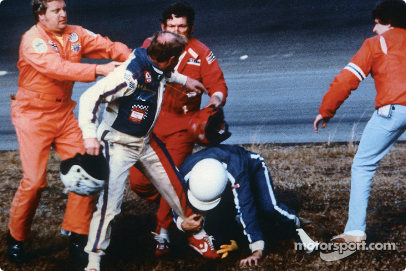 Cale Yarborough holds his helmet in his right hand while fighting off Bobby Allison with his left leg and Bobby's brother Donnie