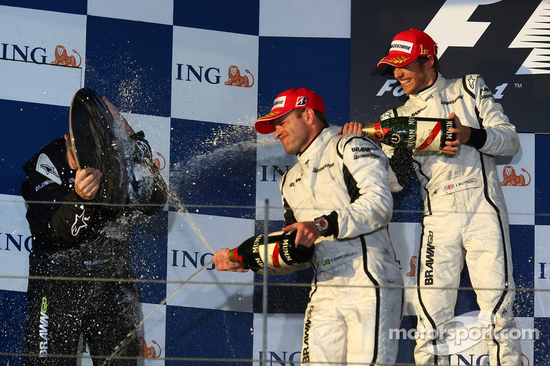Podium: Ross Brawn uses his trophy to keep himself dry from Rubens Barrichello and Jenson Button