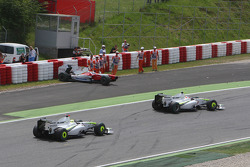 Rubens Barrichello, Brawn GP and Jenson Button, Brawn GP passing the damaged car of Jarno Trulli, Toyota F1 Team