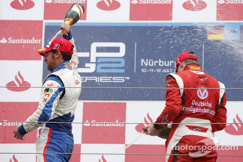 Nico Hulkenberg celebrates his victory on the podium with Roldan Rodriguez
