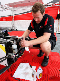 A Formula Two engineer works on a car