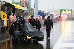 Un Renault Sport F1 Team RS16 es empujado hacia abajo de los boxes en un circuioto un húmedo y lluvioso