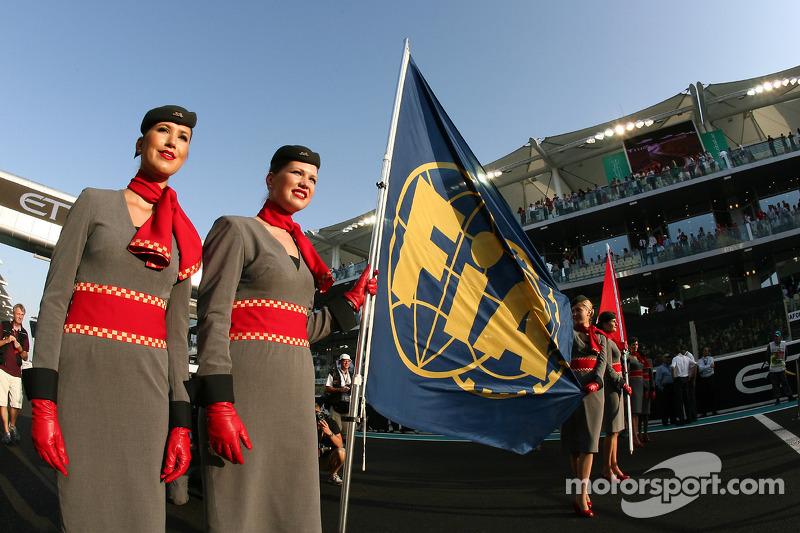 Chicas de la parrilla y la bandera de la FIA