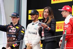 Переможець гонки Льюїс Хемілтон, Mercedes AMG F1 cсвяткує на подіумі з Максом Ферстаппеном, Red Bull Racing, друге місце, та Кімі Райкконеном, Ferrari третє місце, Ноемі де Мігеле, тележурналістом